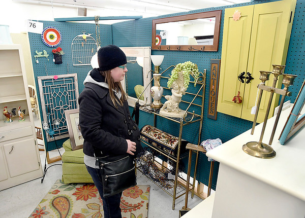 Ashley Hosier, of Anderson, looks over the items in this booth that are for sale as she shops at Emporium 1101 looking for bargain.