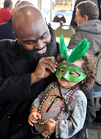 Michael Bounds has fun playing with his one year-old daughter Julianne Eve Bounds as he dresses her up with beads and a Mardi Gras mask while they attend the Fat Tuesday Community Lunch at the Christian Center. A authentic Cajun meal was served up for the center's fund raiser.