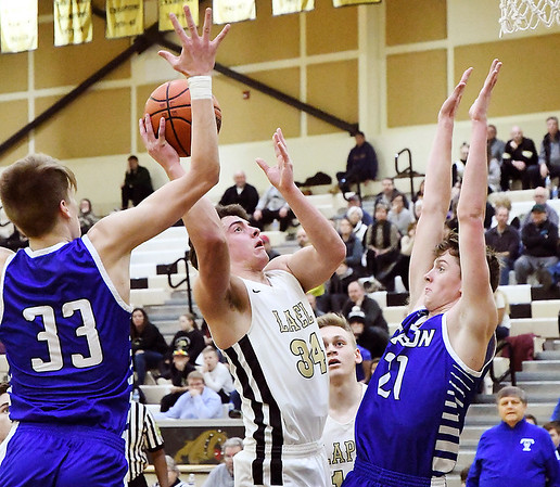 Lapel's Cole Alexander drives the lane to the basket between two Tipton defenders for a shot.