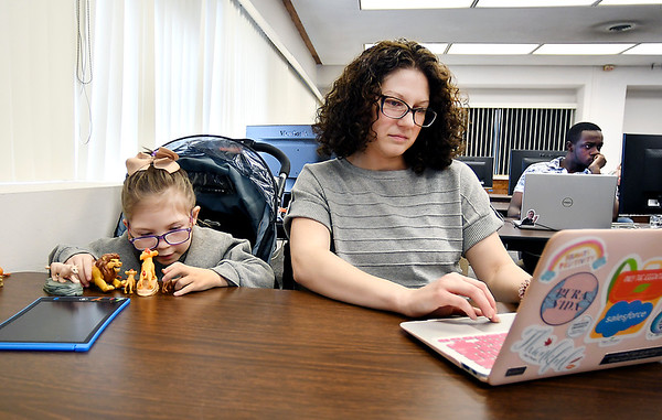As Lily Ann Maynard, 6, plays quietly her mother, Stephanie Maynard, works on her laptop in her Senior Design II computer science course at Anderson University. Maynard home schools Lily Ann and also takes her to her AU classes.