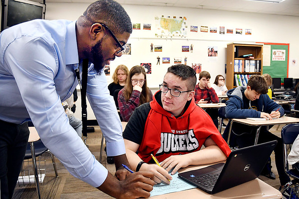 Anderson High School history teacher Darren Oliver answers a question for sophomore Nicholas Cooper in his U.S. Wars history class.