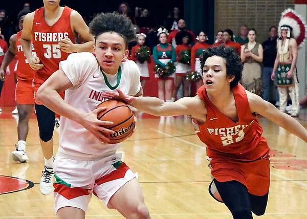 Fishers Bryce Williams gets a hand on the ball as Anderson's Eric Troutman drives the lane.