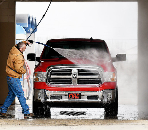 This guy uses the high-pressure spray to get the road grime off his truck  at The Wash Tub car wash on Broadway in Anderson Monday. With the weather forecast, he could have just waited later in the day for the rains to move in and let mother nature wash off the dirt for him.
