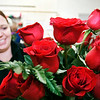 Danielle Latta works on this arrangement of a dozen red roses Thursday at Toles Flowers as they prepare the many orders they've received for Valentine's Day.