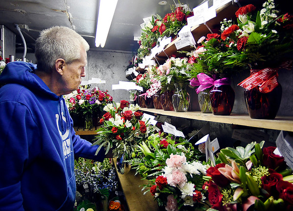 Rob Lenhart puts another finished flower arrangement in the cooler Thursday as Toles Flowers was preparing for Valentine's Day. The shelves of the cooler were full of flowers all to be delivered Friday for Valentine's Day.