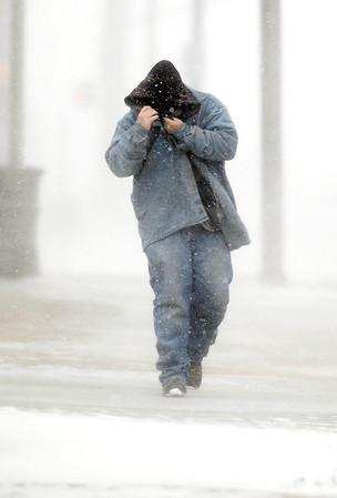 This man tries to protect himself from the bitter cold and gusty winds as he walks along Jackson Street Monday afternoon through a snow shower.