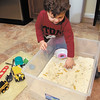 Isaac Fair, 3, plays in his rice box on the kitchen floor.