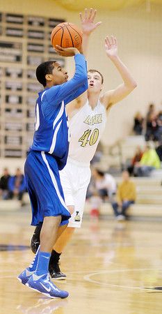 APA's Leo Harris shoots as he is guarded by Lapel's Drew Norton on Friday.
