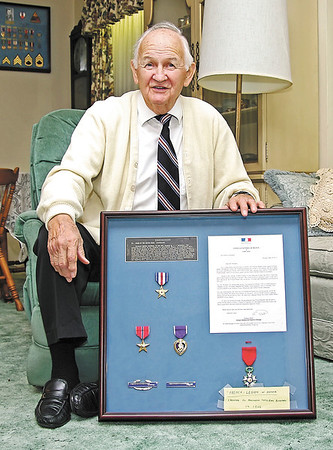 Decorated veteran Dan Brinduse discussing the Knight of the Legion of Honor medal (lower right) which was bestowed upon him by the government of France in recognition of his service to that nation during World War II.  The colors in his custom-made tie mirror those of the ribbon on his Silver Star (upper left); also in the display are his Bronze Star, Purple Heart and Combat Infantry badges.  Visible in the background are additional awards and insignia from his military service.