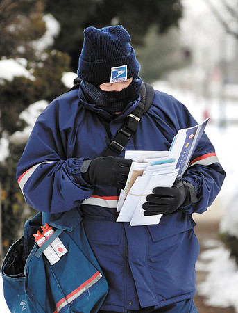 US Postal Service letter carrier Jeff Fudge battles the cold all bundled up as he delivers the mail along West 5th Street Thursday afternoon.