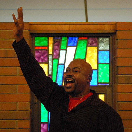 Pastor Samuel Jackson raises his hand as he sings along with the Anderson Community Choir.
