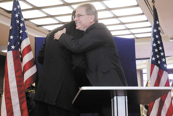 Surveyor Patrick Manship hugs his son Jason after taking the oath of office during a swearing in ceremony at the Madison County Government Center on Tuesday.