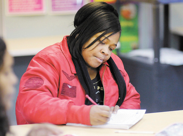 Vevie Sykes looks over a handout during her American Studies class at the Excel Center on Wednesday. The Excel Center has received a teacher performance grant.