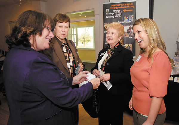 Anna Hinton, left, of PIP Printing and Document Services, exchanges business cards with Nancy Carpenter CPA, Georgeann Whitworth of PNC Bank, and Ariana Khajenouri of PNC Bank, as they network before the start of the monthly FAB luncheon held Friday at The Edge.