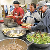 From left, Tom Foudray,  Chuck Shigley and Mike Bowling serve dinner at The Christian Center on Thursday. The center serves around 80 meals a day and that number increases towards the end of the month when more people need food assistance.