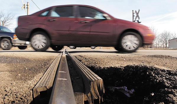 Cars travel south along south Scatterfield Road where they cross several railroad crossings.