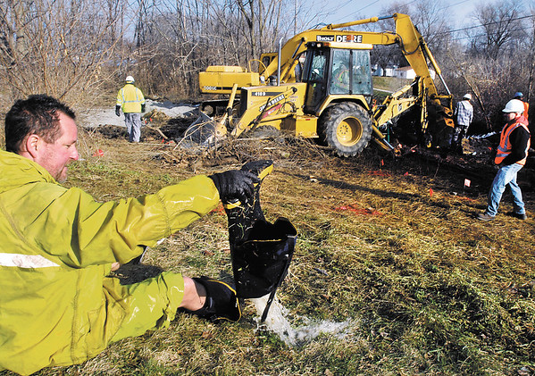As city employees continued to work Thursday to repair a main water line leak that began Wednesday afternoon around 3 p. m. along White River near the Indian Trail Parkway, Water Department worker Todd Long empties his boots of water after being down in the hole to help locate the water pipe.