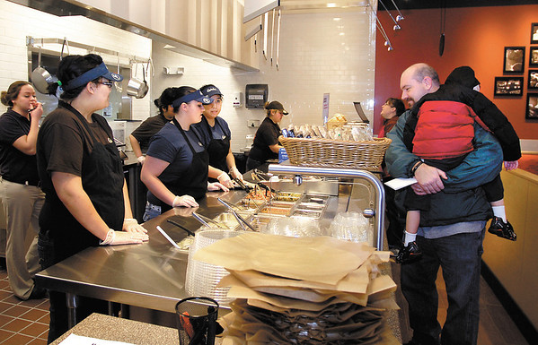 Keith Martin watches as his order is put together at Qdoba Mexican Grill Monday during their grand opening as he was the first customer to be served.