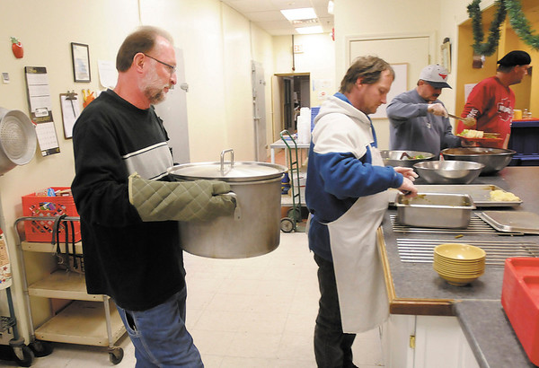 Amos Carmichael, a volunteer minister at The Christian Center, brings a fresh pot of chicken noodle soup to the serving line during dinner on Thursday.