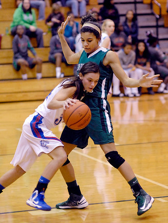 Elwood's Jessie Noone tries to drive through Pendleton's Kiawna Cottrell in their semifinal game of the Girls Madison County Basketball tournament.