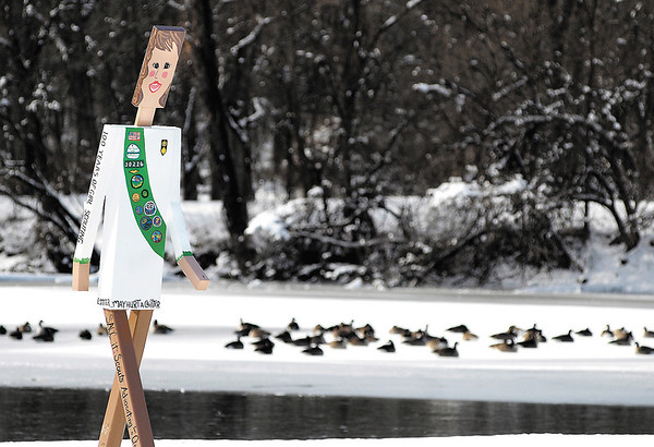 As these Canada geese find refuge from the cold gathered on the snow covered ice of Shadyside Lake this Walking Man girl scout figurine seems not to be bothered by the cold temperatures as she overlooks the geese from her spot on the bank.