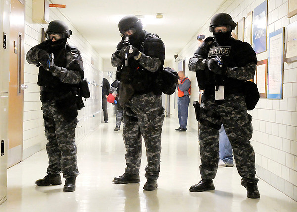 Three APD SWAT officers cover the hallway as a simulated shooting victim is moved  as they run through three shooting scenarios as part of their training at Anderson Preparatory Academy on Wednesday.