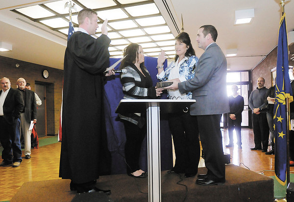Coroner Marian L. Dunnichay is sworn into office by Elwood Judge Kyle Noone as her husband Ned and daughter Danielle look on during a swearing in ceremony at the Madison County Government Center on Tuesday.