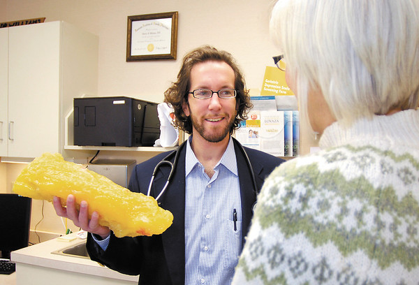 Dr. Charles Williams talks with patient Jerilyn Davis and shows her an example of the size of what 10 pounds of body fat represents.