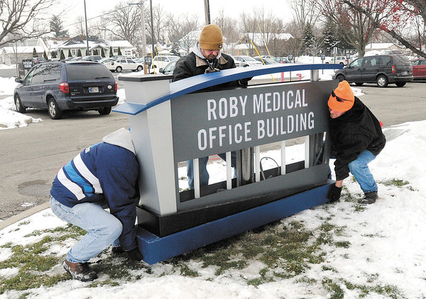 From left, Lonnie Gannom, Chris Hite and Ed Hicks with Premier Sign Group install a new sign for the Roby Medical Office Building as signage is replaced to reflect the new name of the St. Vincent Anderson Regional Hospital.