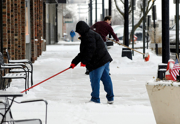A weak weather disturbance moved through early Friday morning dropping about two-inches of light powdery snow over the area.  Here these folks used push brooms to clean off the light stuff from in front of their businesses along Meridian Street.