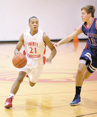 Liberty Christian's Chris Nunn brings the ball down court as he is guarded by Elwood's Steven Fletcher on Tuesday.