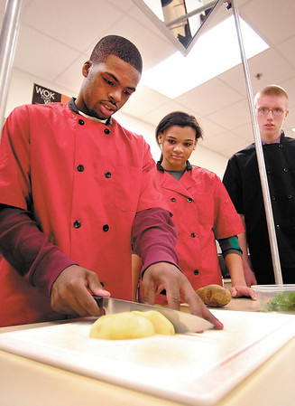 AHS home ec students Kenya Wilkerson, Chelsea Bentley, and Nick Palmer work on peeling, chopping and cubing vegetables for a golden cream soup recipe in Nancy Gates class.