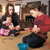Courtney Fair plays with her son Isaac, 3, as they make bracelets out of pipe cleaners and colored beads while holding her 5 month old daughter Cana.