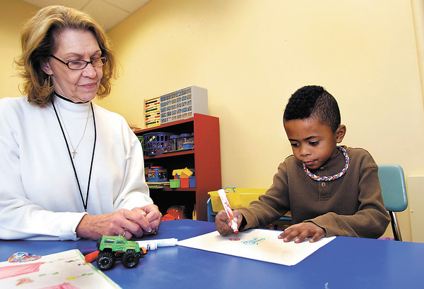 Dr. Sharon McNeany, director of behavioral health services at Madison County Community Health Center, works with Alexandria-Monroe Elementary kindergartener Carson Wood in the Community Health Center's school-based behavioral health care program at the school.