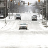 The cold, windy weather brought snow showers through the area Monday with some dropping enough snow to cover the roadways like this view along Jackson Street.