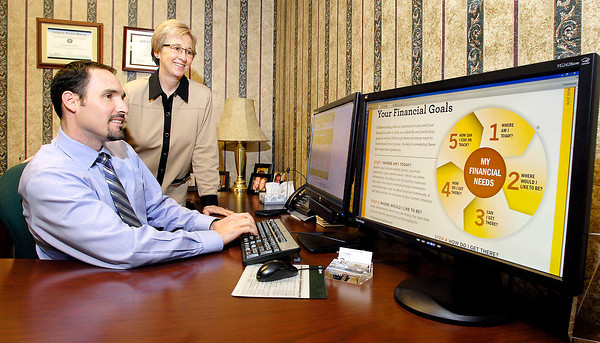 THB photo/John P. Cleary<br /> Cody Hooker, Edward Jones financial advisor, and Connie Sones, Edward Jones branch office administrator, go over items in their offices at 1125 Broadway in Anderson.