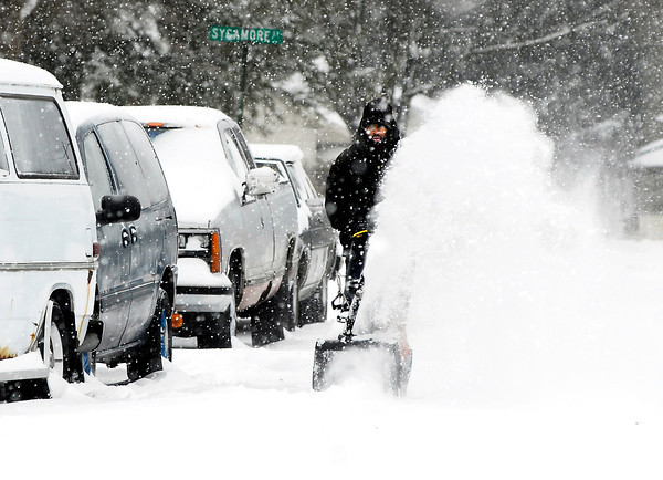 THB photo/John P. Cleary<br /> Quentin Collier snow blows the street in front of his grandfathers house in the 1500 block of west 15th Street to help get the vehicles out after snow fell over the area overnight and continued most of Thursday.