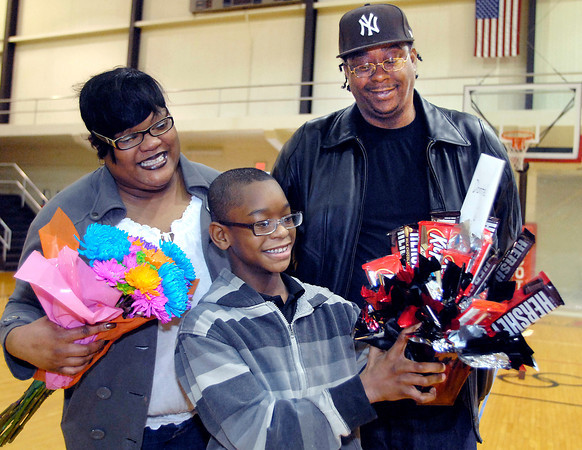 THB photo/John P. Cleary<br /> Highland Middle School sixth grader Donte' King, 12, admires the candy basket her received as his parents, Tisha and Donte' Sr. King look on.  Donte' was selected to be the recipient of the efforts by the newly formed Sparrow Club at Highland to help with his medical bills dealing with spina bifida and needing a new kidney.
