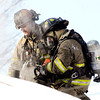 THB photo/John P. Cleary<br /> Anderson firefighters Capt. Matt Cole and Sgt. Dave Cravens cut a hole in the roof of a house at 2702 West 18th Street Thursday morning after a fire broke out in the attic area.