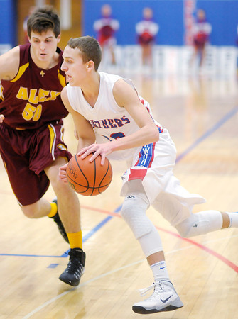 Don Knight / The Herald Bulletin<br /> Elwood's Griffin Hughes drives to the basket as he is guarded by Alexandria's Jonah Jerrils on Friday.