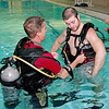 Assistant instructor Shawn Watson assists Heath Weber in putting on an air tank during the introductory scuba diving class at the YMCA.