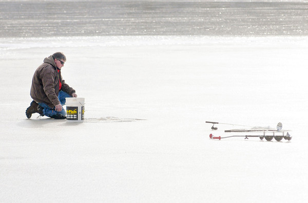 Don Knight / The Herald Bulletin<br /> A fisherman tries his luck on the ice at Rangeline Nature Preserve on Saturday.<br /> <br /> Canadian Geese walk across the frozen surface of the lake at Shadyside Park on Saturday.
