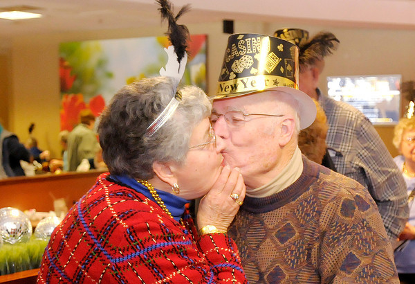 Don Knight / The Herald Bulletin<br /> Hellen Gounaris kisses her husband of 58 years Antonios following a New Year countdown during an early New Year's celebration for the 55-and-older crowd at Hoosier Park on Tuesday.
