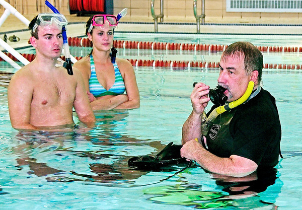 Instructor Les Hiatt demonstrates breathing through the primary air hose and regulator to the YMCA introductory scuba diving class as attendees Rick Simpson and Megan Farver look on.