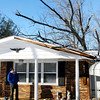 THB photo/John P. Cleary<br /> Doug Lum looks over the damage to his house from this oak tree that was  blown over from high winds Late Sunday night as a cold front blasted through the area bringing the gusty winds and bitter cold temperatures with it.
