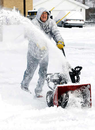 THB photo/John P. Cleary<br /> David Adams uses a large snow blower to help clean off the parking lot of a friend along east 10th Street Thursday morning after 5 inches of snow fell over the area overnight.