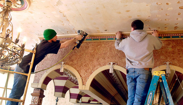THB photo/John P. Cleary<br /> Josh Ashby and Tyler Elliott, of Paul Shively Construction, put up new trim pieces around the ceiling in the concession area of the Paramount Theatre Wednesday.  The historic facility suffered water damage last week after a water line broke in the second-floor kitchen flooding the Marquee Room and damaging the first-floor concession area. Paramount executive director Gayle Jones Burris said concessions will be available this Friday for the Open Jam being held in the theater and that repairs should be completed by mid next week.