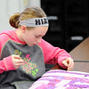 Don Knight | The Herald Bulletin<br /> Johnna Hiatt, 10, stitches the edge of a quilt during a meeting of the quilting club at Summitville Elementary on Wednesday. The club is making three quilts to be auctioned off in February as a fundraiser for the school