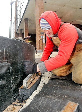 John P. Cleary    The Herald Bulletin<br /> Darrek Britton levels bricks as he, along with his co-workers from M & S Masonry, Inc. of Pendleton, lays bricks around the landscape area on the southwest corner of the Madison County Government Center plaza Monday afternoon.