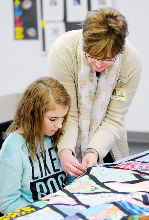 Don Knight | The Herald Bulletin<br /> Shellie Crowe helps Jovi Southard while she works on a quilt during a meeting of the quilting club at Summitville Elementary on Wednesday.